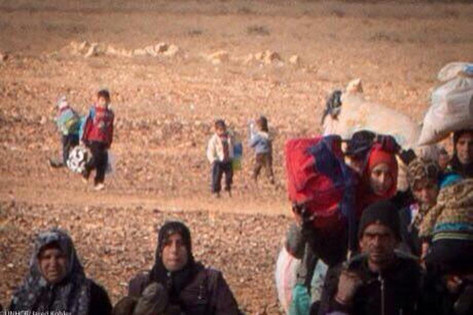 La fotografía muestra a Marwan caminando (al centro) y adelante el grupo de refugiados donde iba su familia