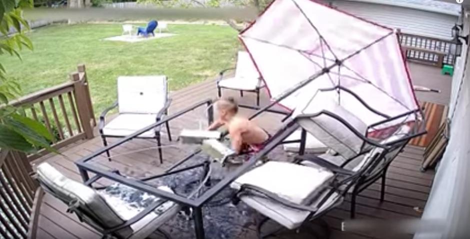 El niño no cae el suelo, queda agarrado de uno de los soportes de la mesa. (Captura de pantalla: Daily Mail)
