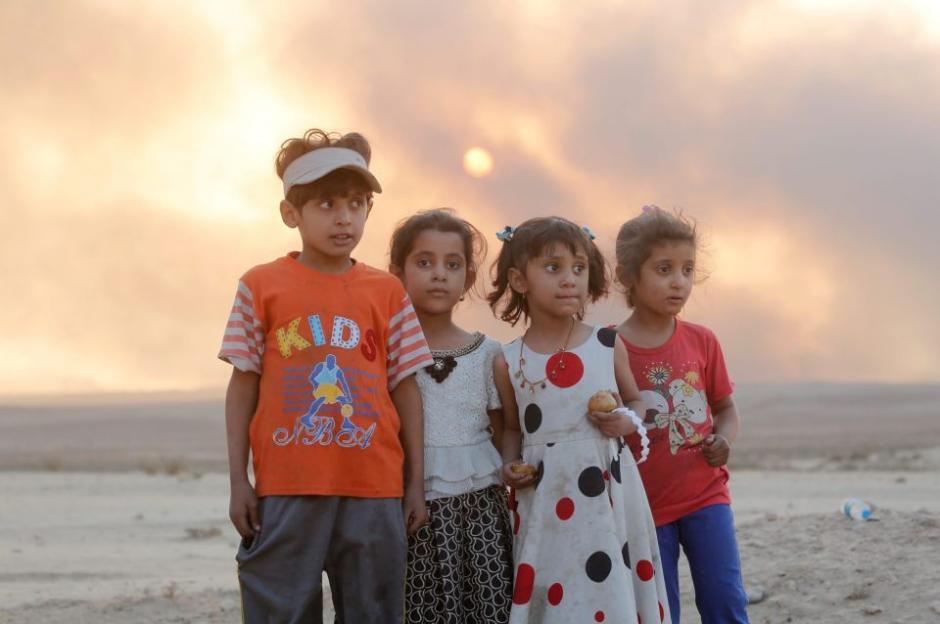 Un grupo de niños observan el avance de las fuerzas armadas que liberan la zona donde viven. (Foto: The Sun)