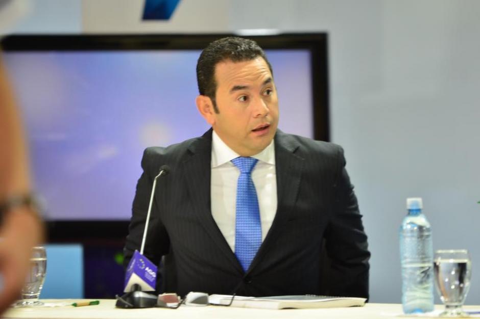 Jimmy Morales captado en un corte comercial ajustando la silla en el debate de la AGG. (Foto: Jesús Alfonso/Soy502)