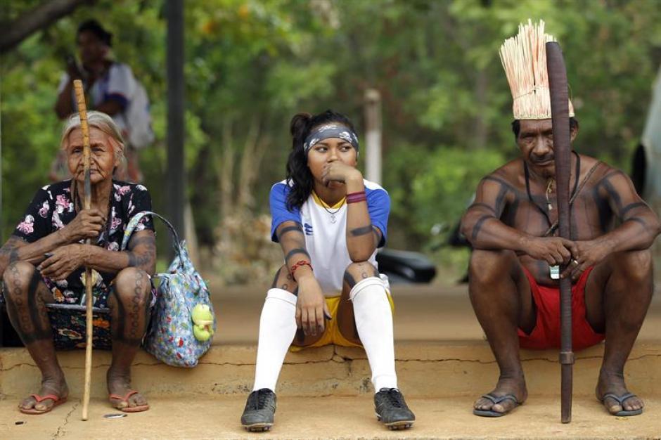Una familia de la etnia Xerente de Brasil, a la espera del inicio de un partido de fútbol femenino de contra la etnia Kaingang. (Foto: EFE)