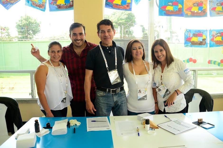 Francisco Páez, vocalista del grupo guatemalteco Malacates Trébol Shop, junto a integrantes de una Mesa Electoral. (Foto: Selene Mejía/Soy502)