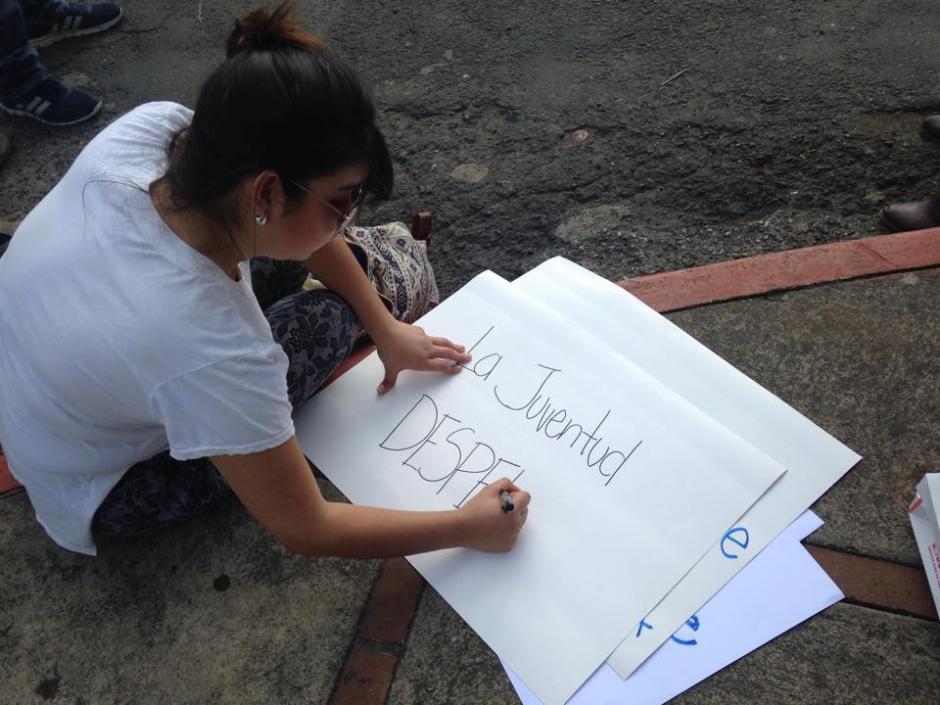 Estudiantes de la Universidad Landívar realizan pancartas para la protesta #27A. (Foto: Fredy Hernández/Soy502)