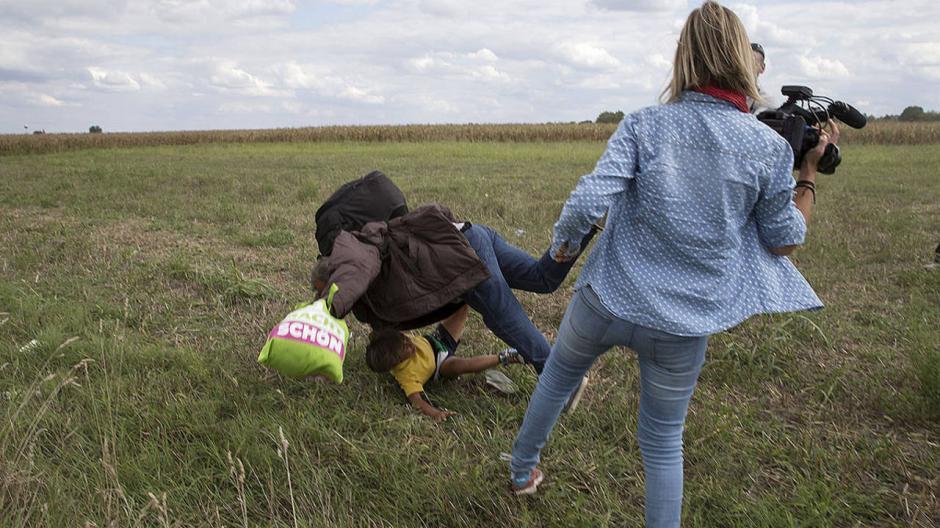 El 8 de septiembre, la reporterade HungríaPetra Lazlo, metió zancadilla al refugiado sirio Osama Abdul Mohsen quien llevaba en sus brazos a su hijo cuando escapaban de las fuerzas de seguridad húngaras para evitar ser detenidos. La noticia llenó de indignación al mundo. (Foto:rtve.es)