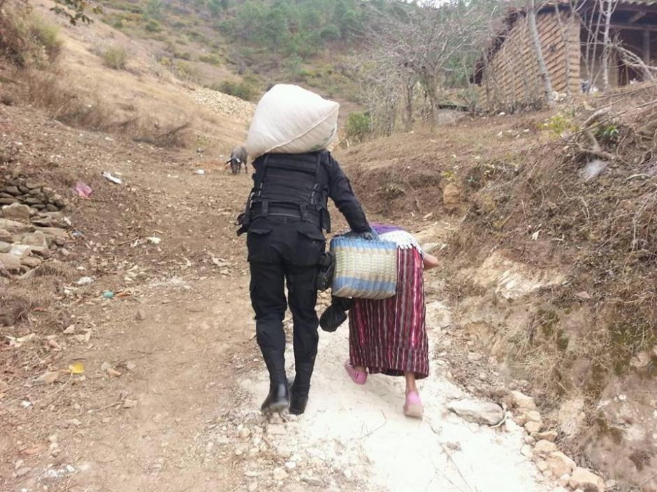 Además de ayudarla con la carga, el agente apoya la señora a subir la pendiente. (Foto: Facebook/PNC San Andrés Sajcabajá)