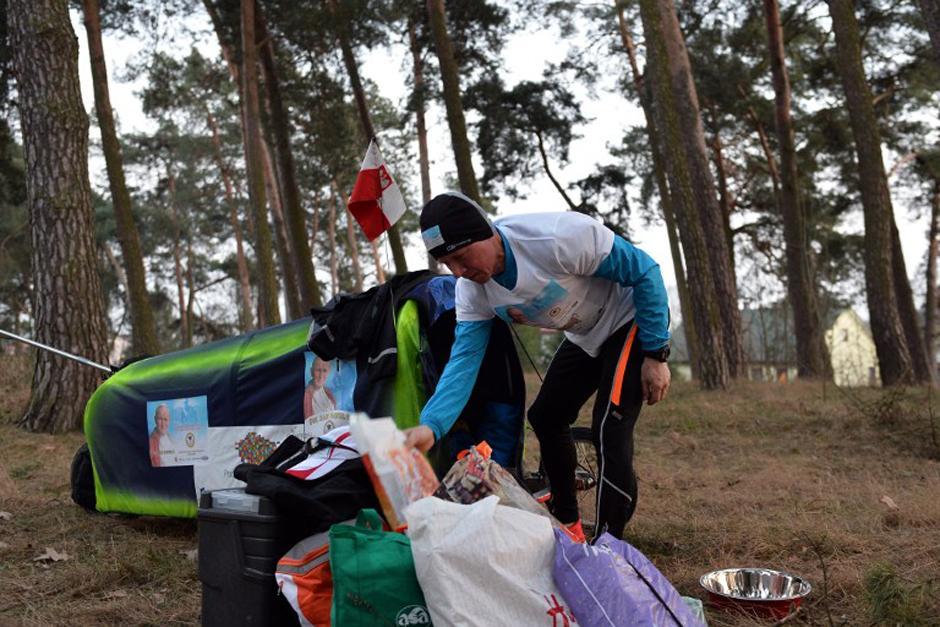 Kurlyo hala un carrito mientras corre, este contiene su vestimenta, zapatos extras, alimentos y libros con oraciones. (Foto: AFP)