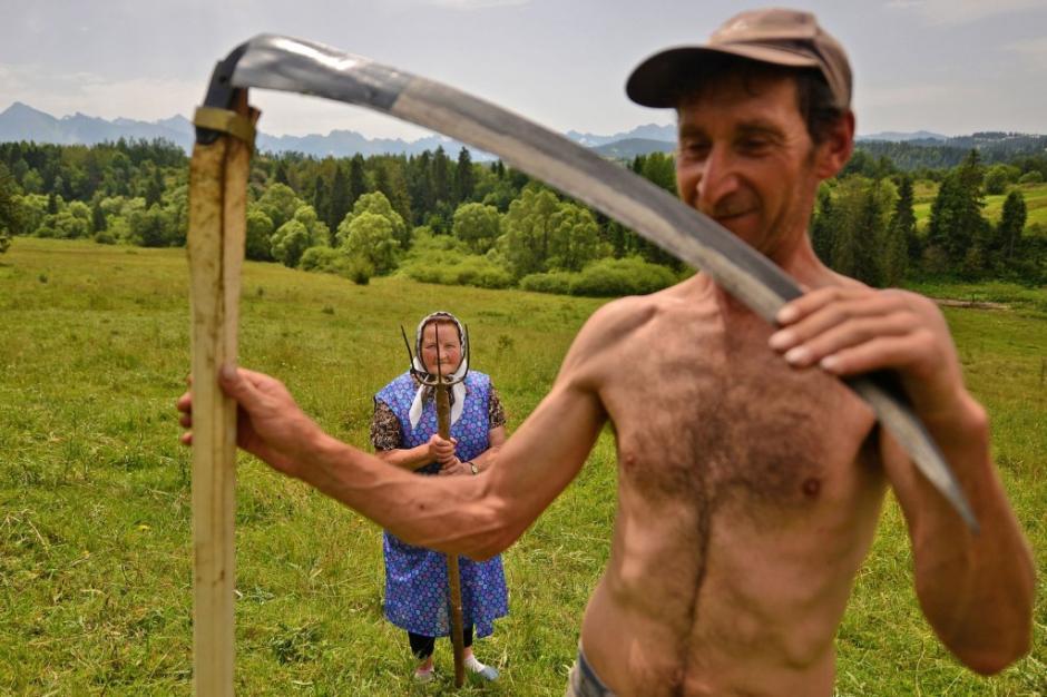 Granjeros en Polonia muestran las herramientas que utilizan para la creación del heno. El hombre sostiene una guadaña y la mujer una horca. (Foto: Bartlomiej Jurecki/National Geographic)