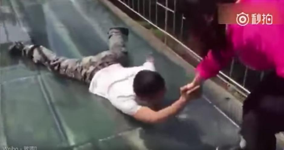 El hombre es arrastrado por el puente para llegar al otro extremo. (Captura de pantalla: Man&Women/YouTube)