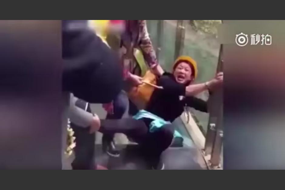 Sus amigos llevan a una mujer a jalones para que pase el puente de cristal. (Captura de pantalla: Man&Women/YouTube)