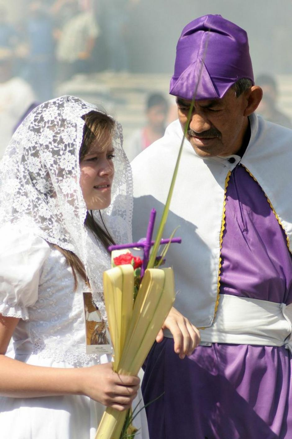 En la procesión de Jesús de las Palmas participan niños y jóvenes. Aquí una cargadora vestida de blanco, asistida por un cucurucho de mayor edad. La tradición se pasa de generación en generación. (Foto: Raúl Illescas).