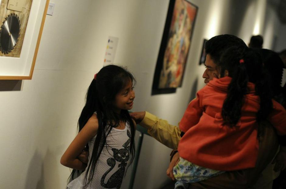 Una niña disfruta de las obras mientras comenta con su padre el significado de las piezas.