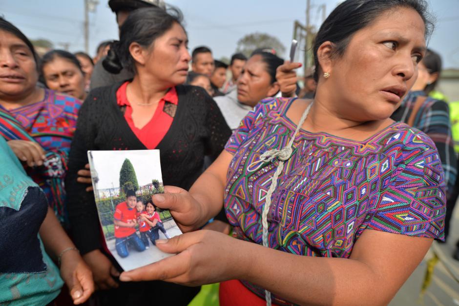 Una señora muestra la foto de uno de los desaparecidos.(Foto: Wilder López/Soy502)