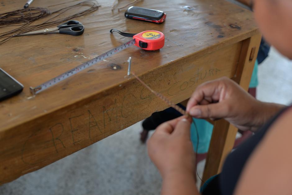 Mujeres trabajan en hacer pulseras para obtener ingresos. (Foto: Wilder López/Soy502)