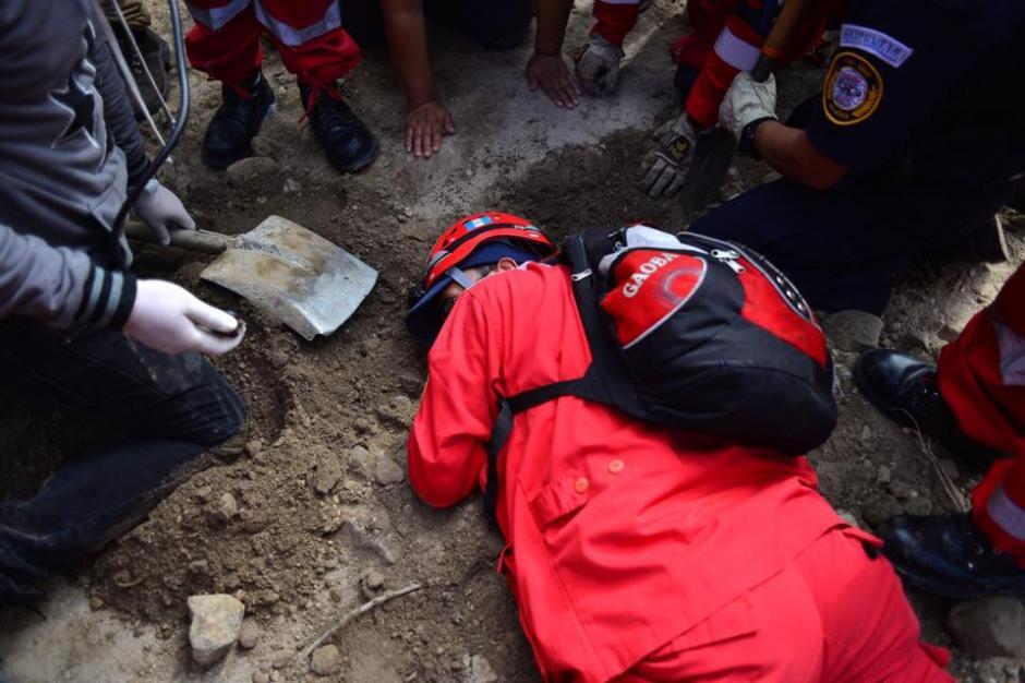 Los rescatistas piden silencio mientras escuchan en el suelo los gritos de ayuda. (Foto: Jesús Alfonso/Soy502)
