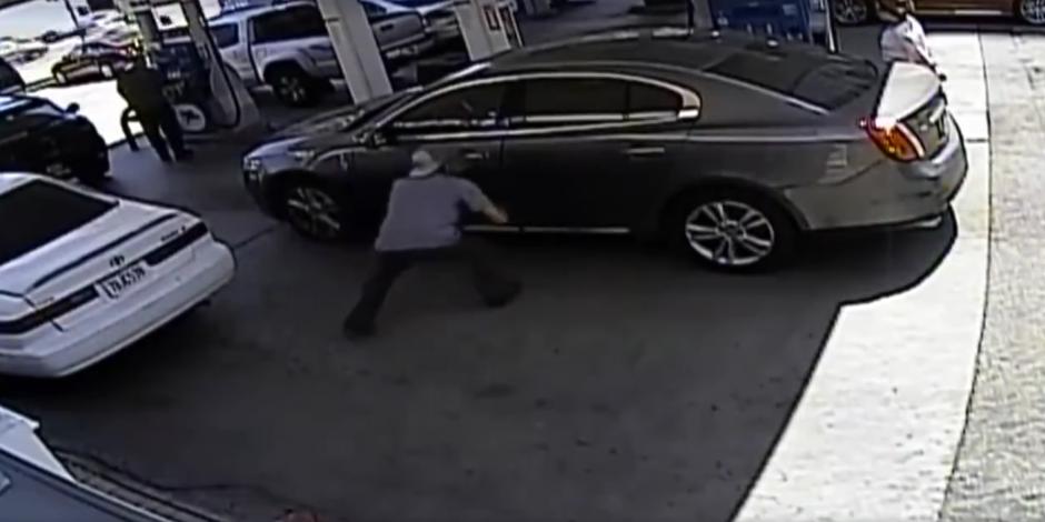 El individuo logra llegar a la puerta del carro, done busca la cartera de la mujer. (Captura de pantalla: Infobae)