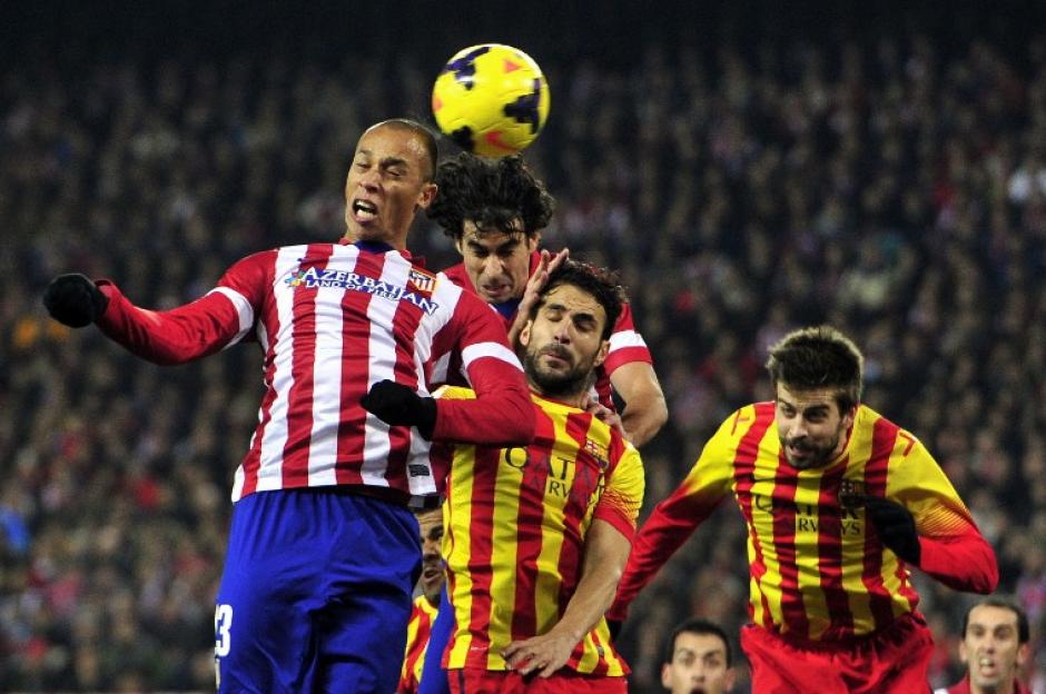 Joa Miranda de Souza (L) salta por el balón durante el encuentro con Atlético y Barcelona. AFP PHOTO/ GERARD JULIEN