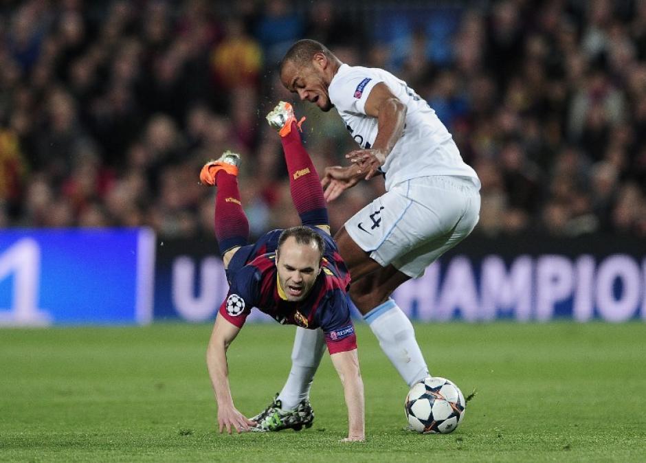 Andrés Iniesta, del Barça, tiene un encontronazo con Vicent Kompany, del Manchester City, en el primer tiempo del partido que se disputa en el Camp Nou. (Foto: AFP)