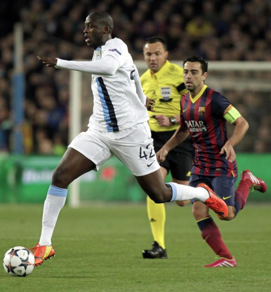 El centrocampista marfileño del Manchester City Touré Yayá avanza con el balón perseguido por el centrocampista del FC Barcelona Xavi Hernández , durante el partido de vuelta de los octavos de final de Liga de Campeones disputado esta noche en el Camp Nou. (Foto: EFE)