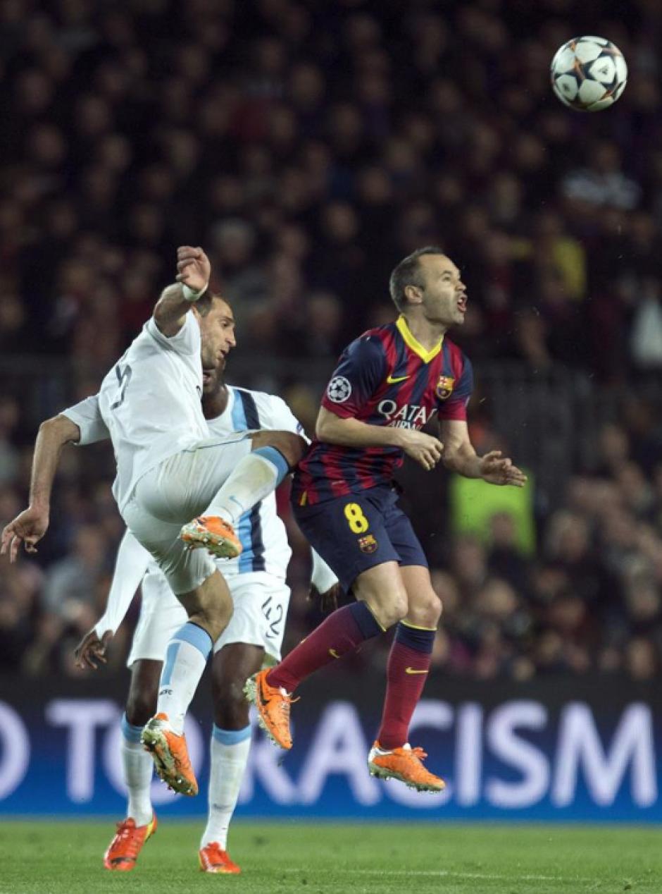 El centrocampista del FC Barcelona Andrés Iniesta lucha un balón con el defensa argentino del Manchester City Pablo Zabaleta, durante el encuentro. (Foto: EFE)