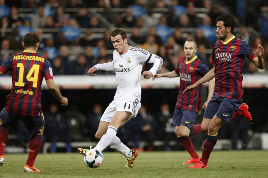 El centrocampista galés del Real Madrid Gareth Bale (c) controla el balón ante el centrocampista argentino del Barcelona Javier Mascherano (i), durante el partido de la vigésimo novena jornada de la Liga de Primera División que se juega hoy en el estadio Santiago Bernabéu. (Foto: EFE/Juan Carlos Hidalgo)