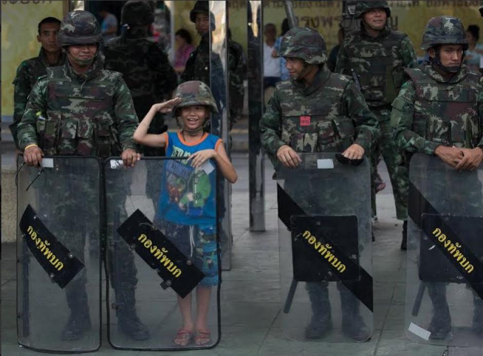 Un niño posa para una fotografía con los soldados tailandeses en Victory Monument, el sitio de las recientes protestas contra el golpe de Estado que ha sido cerrado por las fuerzas de seguridad para evitar nuevas manifestaciones el 30 de mayo de 2014 en Bangkok. (Foto: AFP)