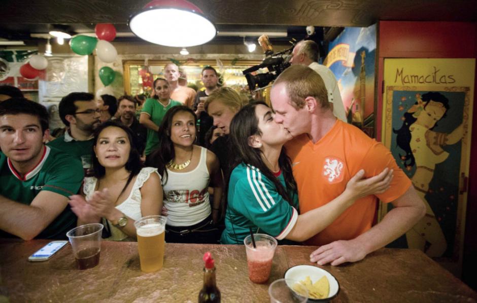 Dos aficionados mundialistas, de México y de Holanda, sellan el resultado del partido con un beso, en un restaurante en Amsterdam. (Foto: EFE)
