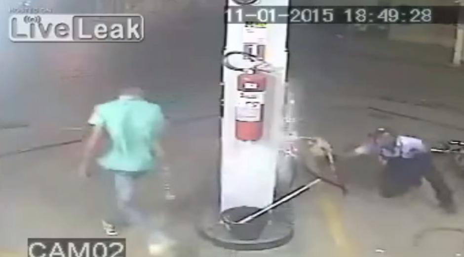 El hombre se defiende con la manguera de combustible.(Imagen: YouTube)