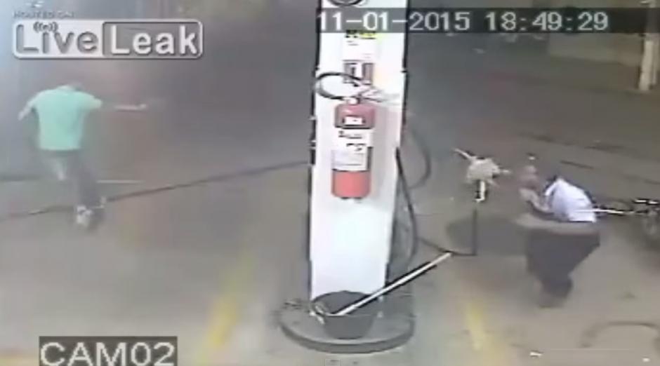 El delincuente le apunta con un arma y el empleado de la gasolinera se defiende con un chorro de combustible.(Imagen: YouTube)