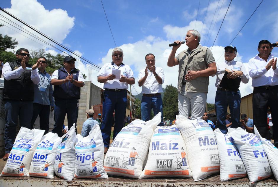 El presidente Pérez Molina participa en la entrega de sacos de alimentos con la imagen de un agricultor vestido con los colores del partido Patriota. (Foto: Presidencia)