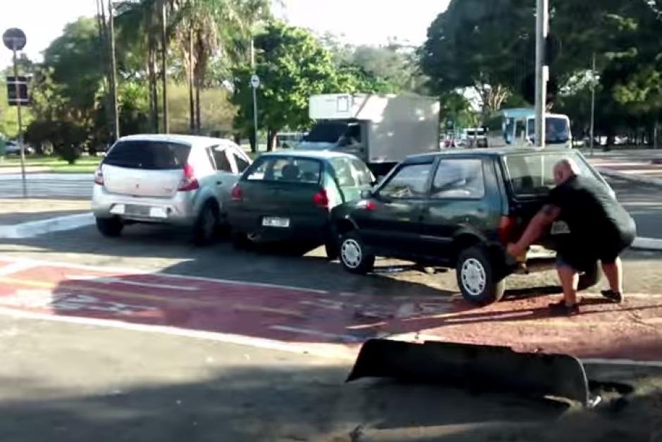 El hombre fuerte se decide a mover el carro sin la ayuda de nadie para que la vía quedara libre.(Captura: YouTube)