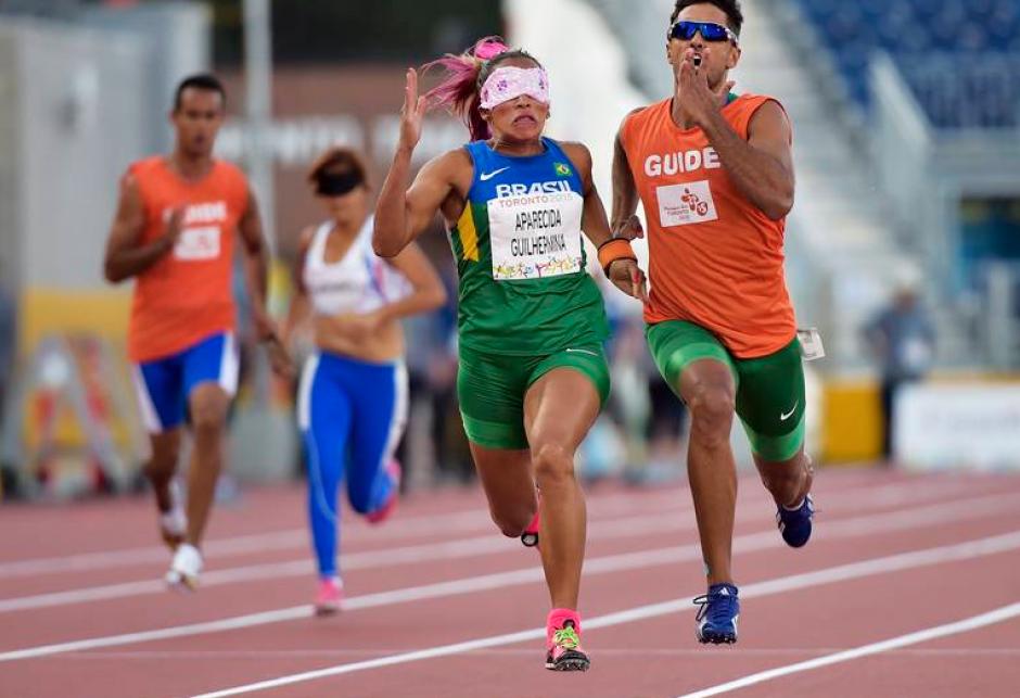La competidora brasileña Aparecida Guilher acompañada con su guía captados durante la competencia de los 100 metros.(Foto: Página oficial de los Juegos Parapanamericanos de Toronto 2015)