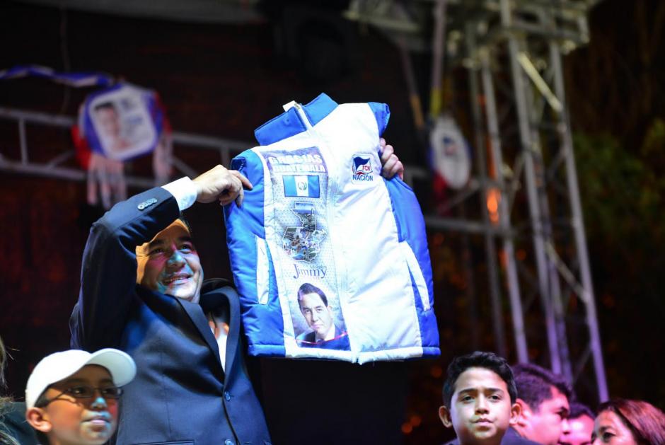 Jimmy Morales muestra un chaleco que le regalaron simpatizantes en el lugar donde se festejaba que ganó la Presidencia. (Foto: Jesús Alfonso/Soy502)