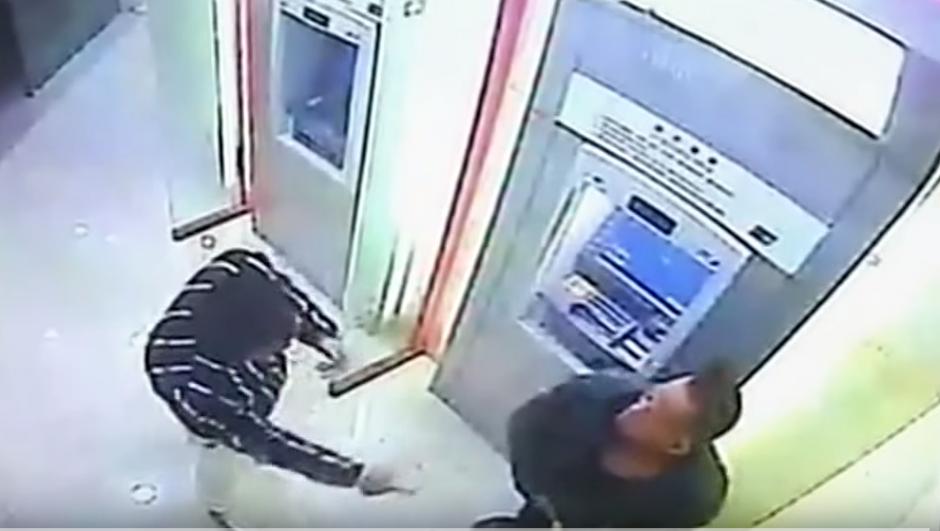 Un delincuente intenta robarle el dinero a un hombre que se encontraba en un cajero automático. (Imagen: YouTube/RT)