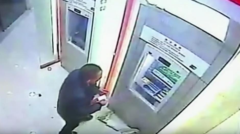 El hombre le da una golpiza al delincuente y retira su dinero del cajero automático.(Imagen: YouTube/RT)