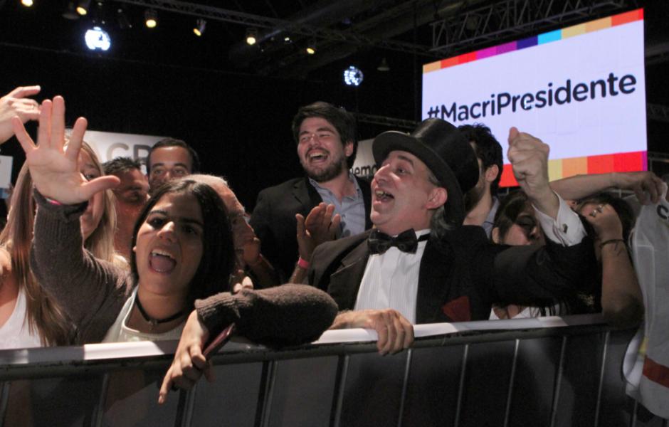 Un grupo de personas celebra los resultados de los primeros sondeos en la sede del candidato opositor Mauricio Macri. (Foto: EFE)