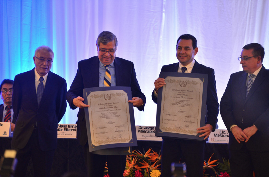Jimmy Morales y Jafeth Cabrera muestran los documentos que los acreditan como las nuevas autoridades del Organismo Ejecutivo. (Foto: Wilder López/Soy502)