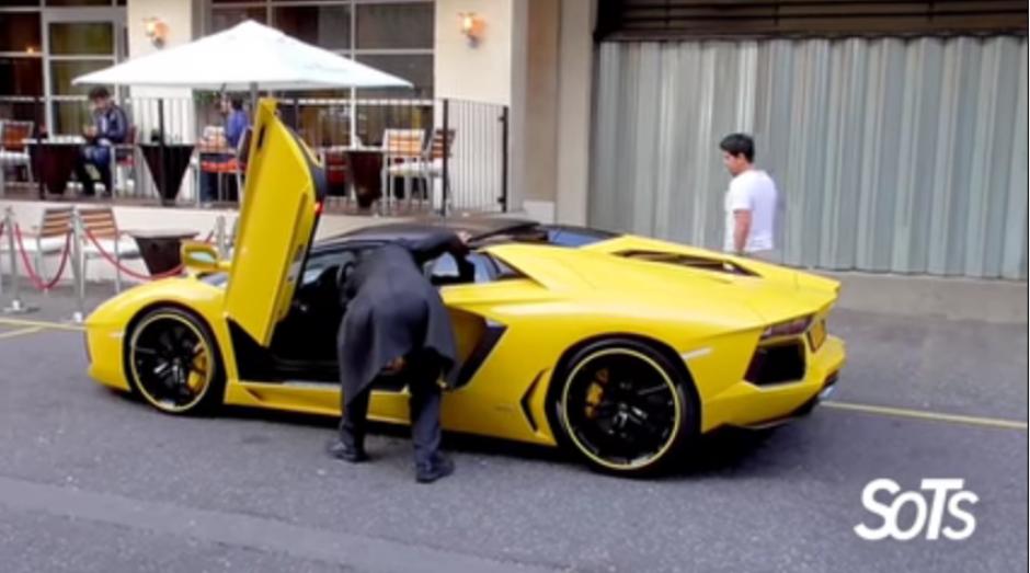 El hombre mira adentro del carro para medir su espacio.