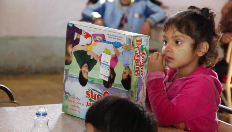 Esta niña espera las órdenes de su niñera para abrir la caja que contiene su nuevo juguete.(Foto: Fredy Hernández/Soy502)
