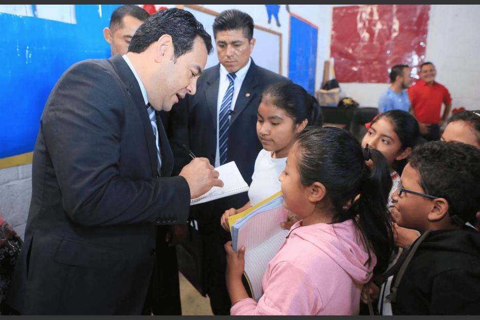 El presidente Jimmy Morales da autógrafos a los niños de la escuela que visitó. (Foto: Presidencia)