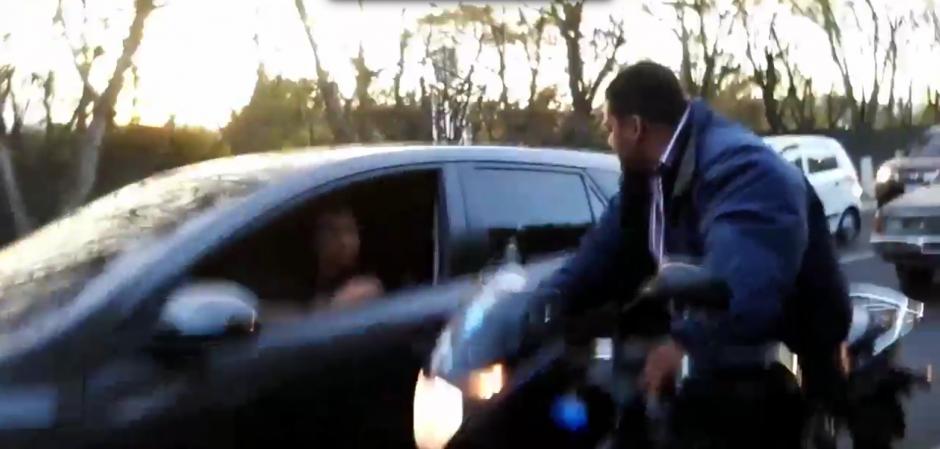 El motorista habla con una mujer en un carro. (Foto: captura de Twitter)