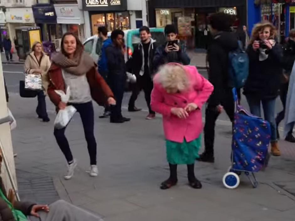 Varios artistas callejeros bailan en la calle junto a una mujer de la tercera edad. (Imagen: Ezda Beevers)