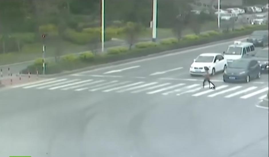La mujer sigue su camino sin prestarle atención al alto que marca el semáforo. (Foto: RT en Español / YouTube)