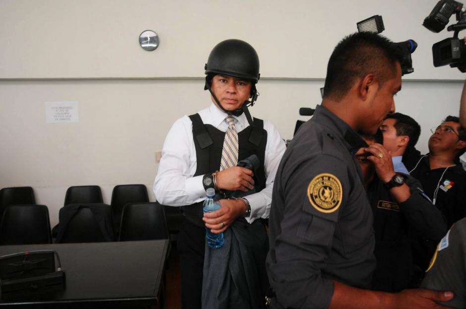 González es trasladado con un chaleco antibalas y un casco, además del dispositivo de seguridad que lo rodea. (Foto: Alejandro Balán/Soy502)
