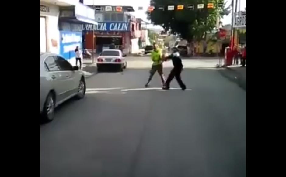 El hombre de verde amenaza al agente con un machete. (Foto: Captura/Facebook)