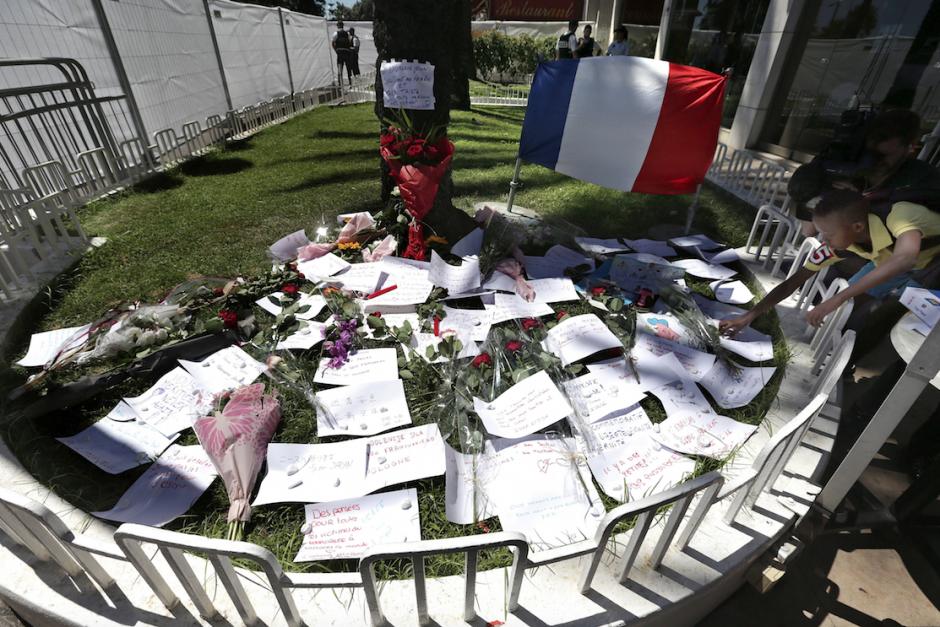 Flores y mensajes de recuerdo y apoyo a las víctimas, junto a una bandera de Francia. (EFE/Alberto Estévez)
