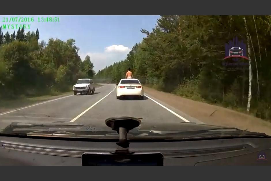 Un conductor grabó el momento en el que la chica va sobre un carro blanco bronceándose. (Captura Youtube)