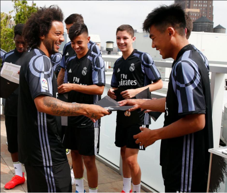 Marcelo le enseña a un joven cómo se hace el saludo con James. (RealMadrid.com)