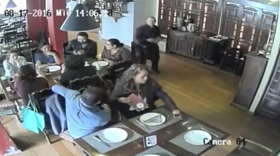 Una pareja se sienta en una mesa cercana a otra donde hay varias personas comiendo y empiezan a observar el panorama. (Imagen: captura de YouTube)