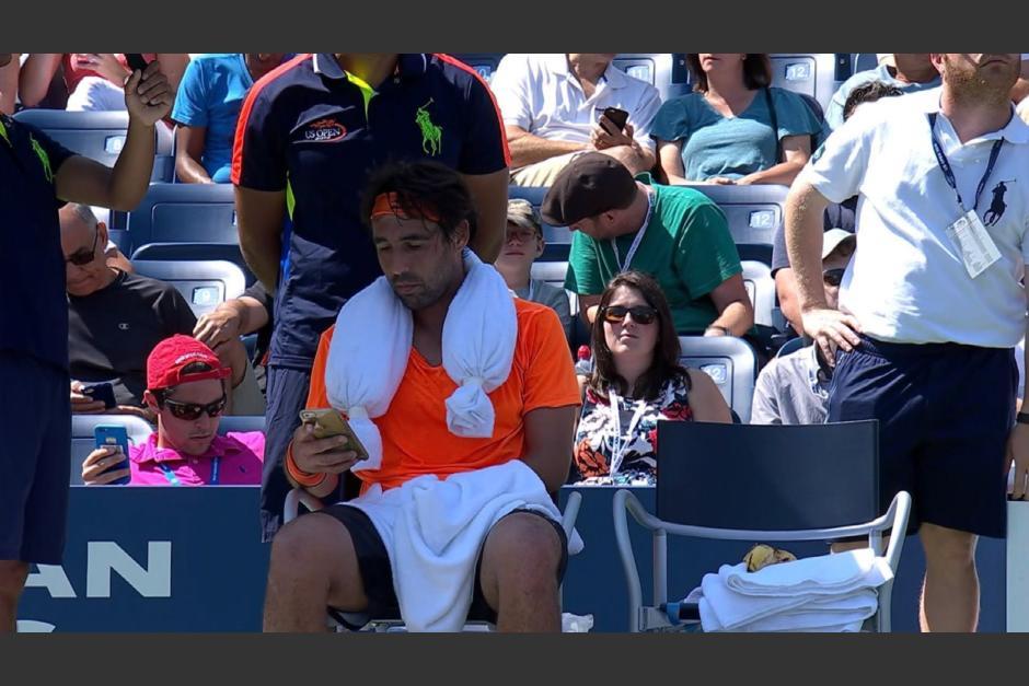 Marcos Baghdatis, está en la banca y con el celular en la mano. (Captura de Pantalla)