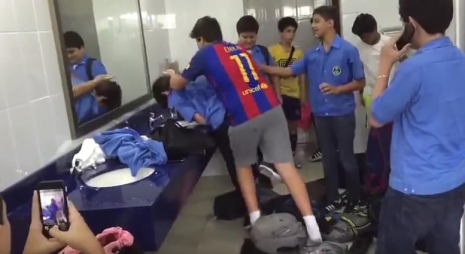 Un niño mayor somete a un compañero en los baños del colegio. (Captura de video)